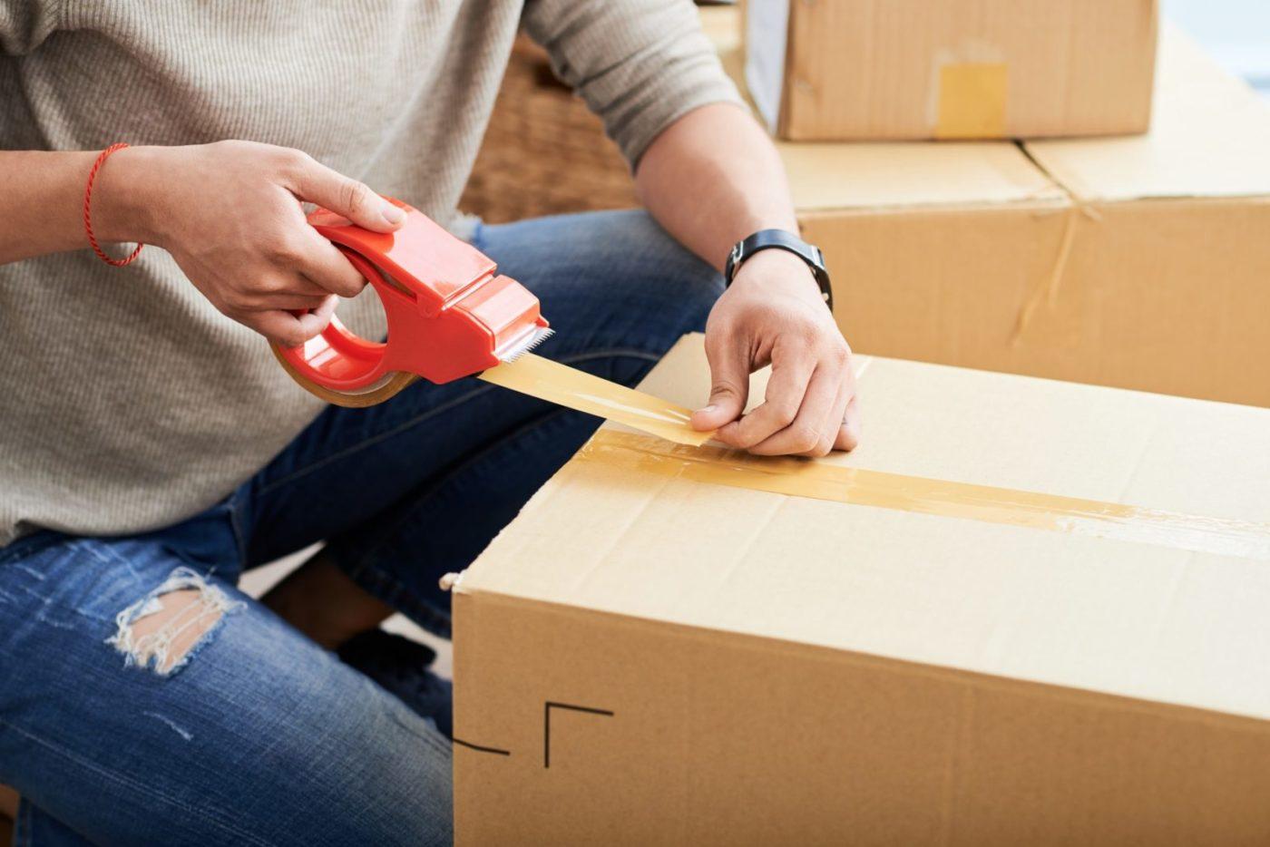 Crop man sealing carton box