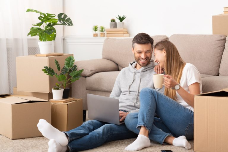 Happy couple sitting among moving boxes and having fun